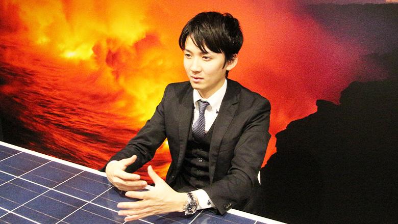 地熱発電の壁紙とソーラーパネルの机がある会議室でインタビューに答えるS.Yさん