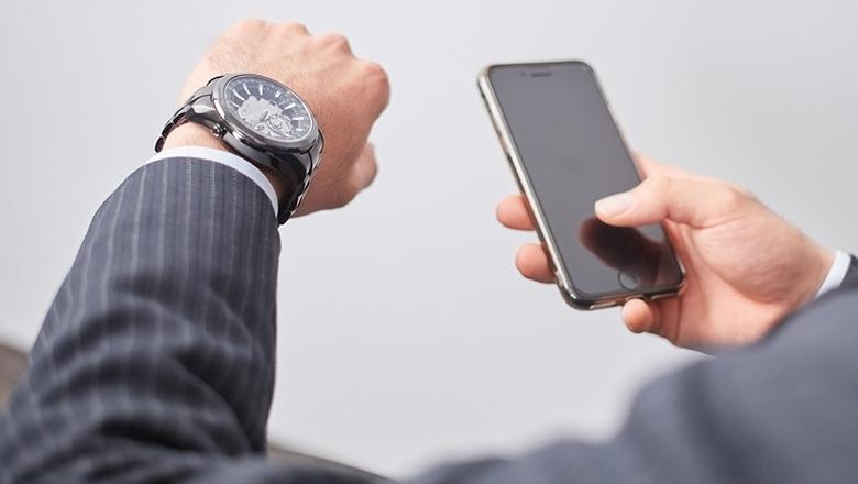 携帯をみながら時間を気にする営業社員